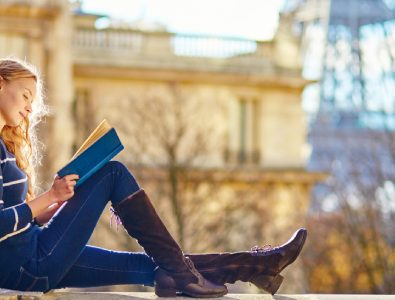 A Young Smiling College Girl Sit In A Place And Studying.