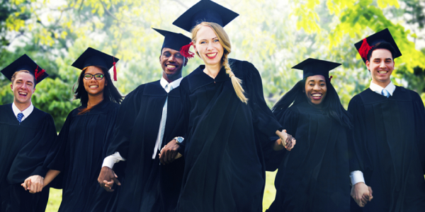 Happy And Young Smiling Graduates In Their Academic Dress.