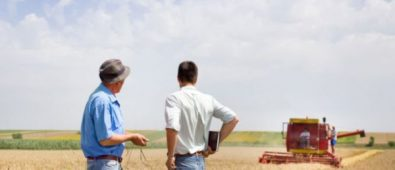 Two Persons Standing On The Ground & Discussing About Farming.