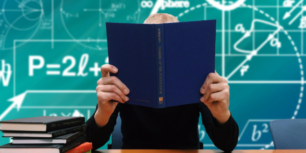 A Person Studying With A Book Hiding His Face.