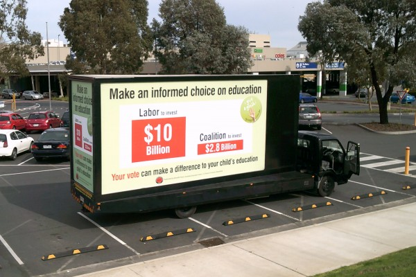 An Attractive Advertisement On A Mobile Billboard Truck Driving Down The Road Which Is About The Higher Education For Students.
